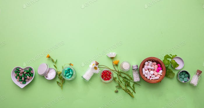 Homeopathy, globules and medicibe on green background