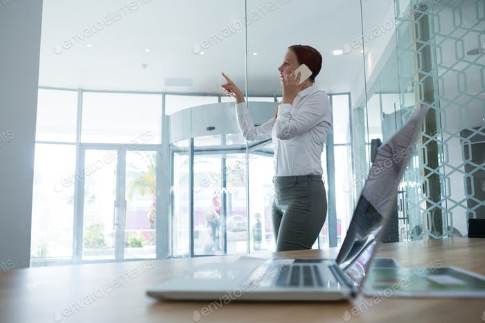Female executive using invisible digital screen while talking on mobile phone