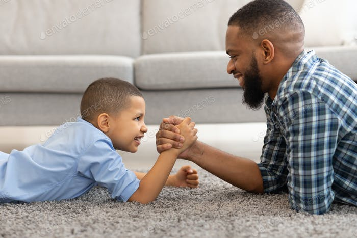 Happy Black Father And Son Armwrestling Lying On Floor Indoors