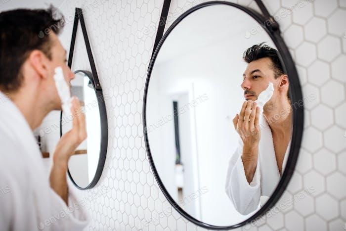Молодой человек бритье в ванной утром, повседневная рутина