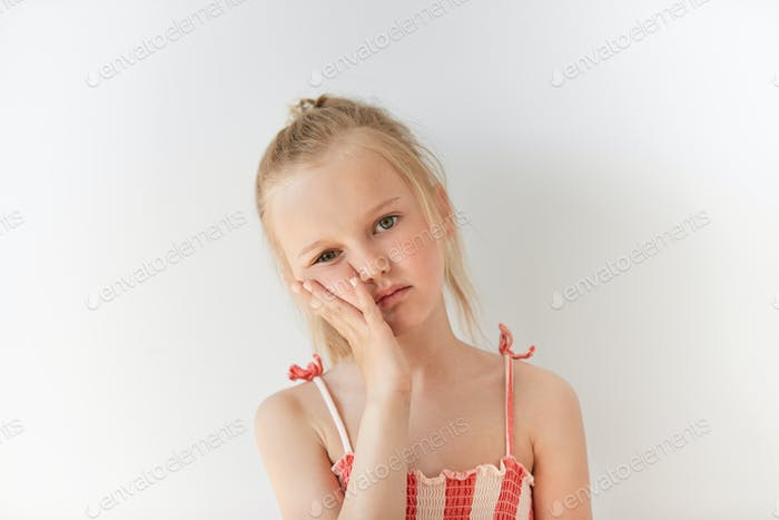 Small Caucasian girl looks tired in morning light indoors. Her facial expression shows boredom and i