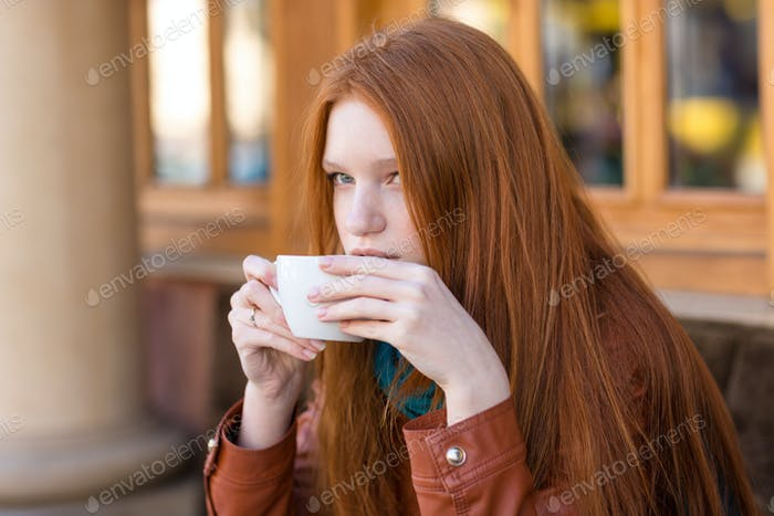 Girl drinking coffee in outdoor cafe