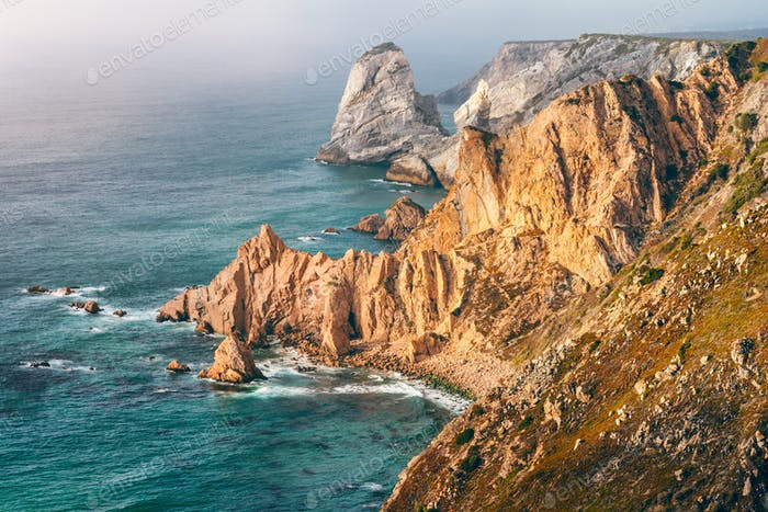 Sintra, Portugal. Rocky coastline between Cape Roca and Praia da Ursa in evening sunset light and