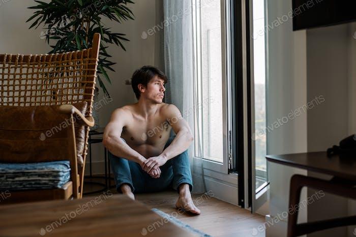 Hombre sentado en el suelo en casa