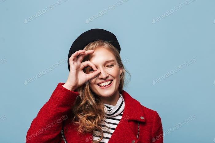 Smiling girl with wavy hair in beret and red jacket playfully looking in camera over blue background