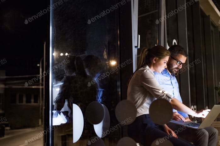 Businesspeople in the office at night working late.