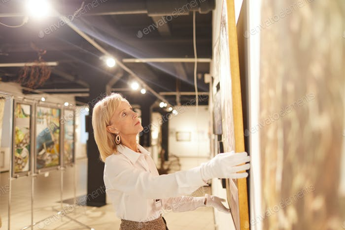 Mature Woman Hanging Paintings in Art Gallery