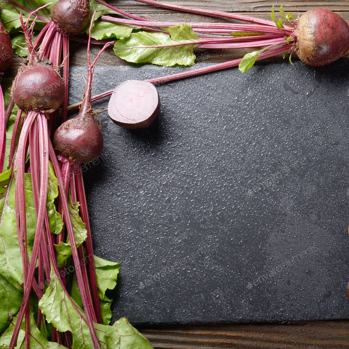 Top view at fresh organic beets with leaves on wooden rustic tab