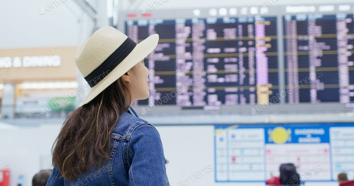 Mujer cheque en el número de vuelo en el aeropuerto