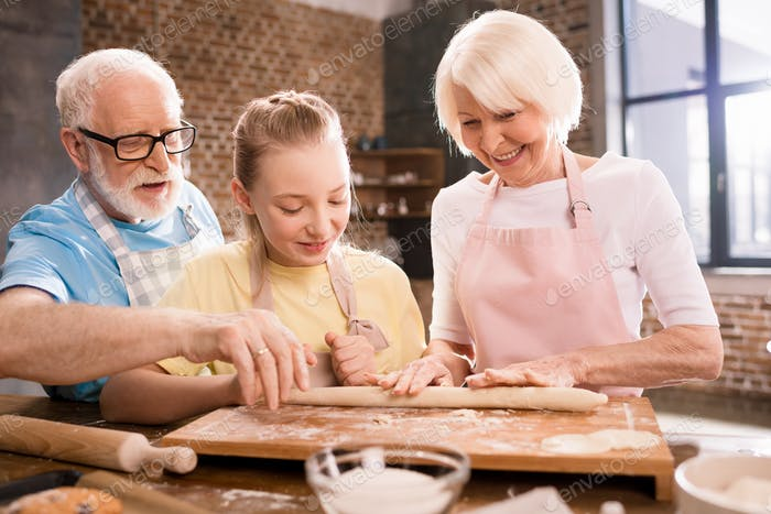 grandmother, grandfather and granddaughter cooking and kneading dough for cookies at kitchen table,