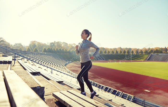 happy young woman running upstairs on stadium