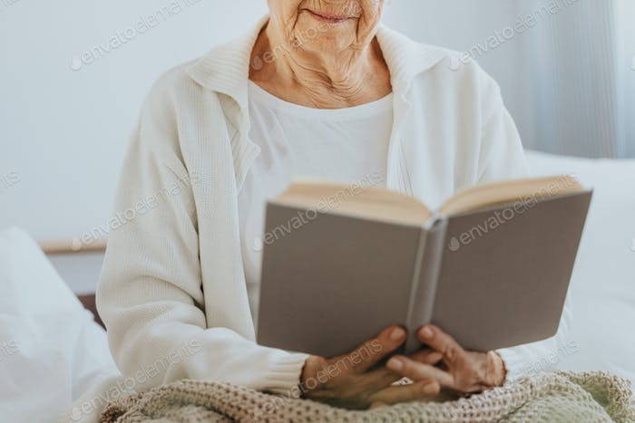 Senior woman reading book in nursing home