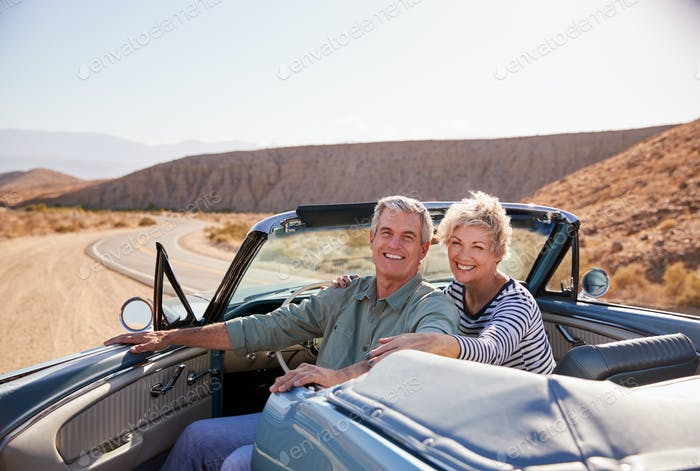 Senior couple smile to camera from parked open top car