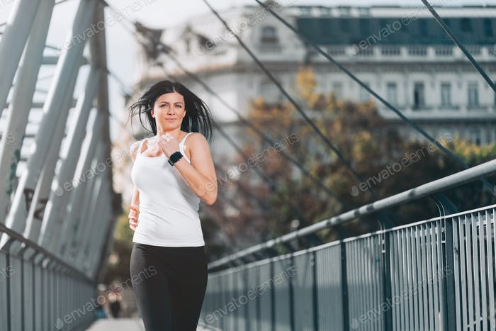 City workout. Beautiful woman running in an urban setting