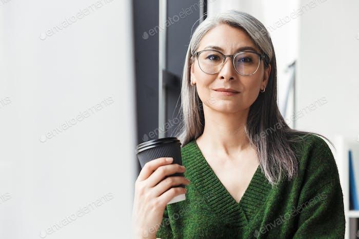 Attraktive lächelnde reife Frau mit langen grauen Haaren stehend