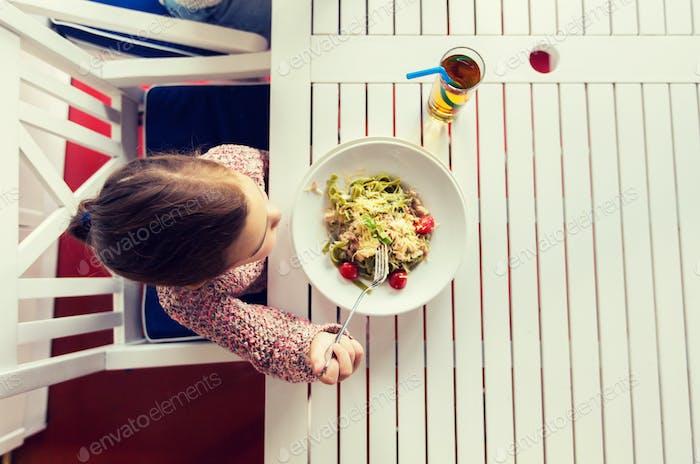 little girl eating pasta for dinner at restaurant