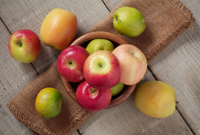 Apples in a bowls on wooden