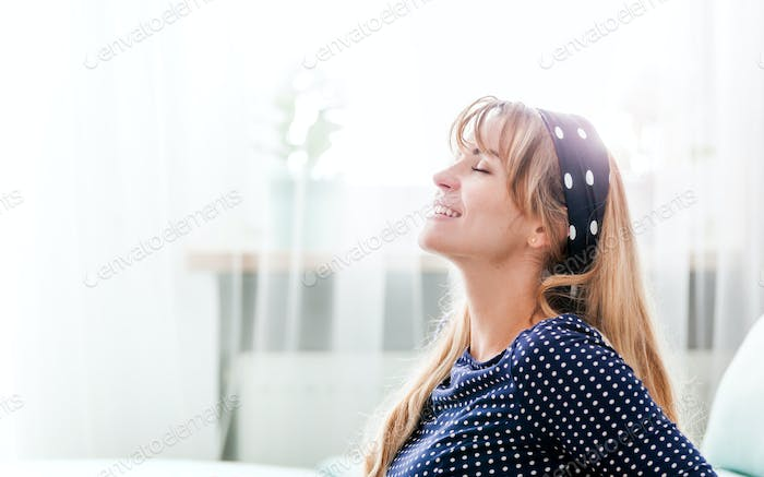 Cheerful smiling young woman at home, positive leisure time