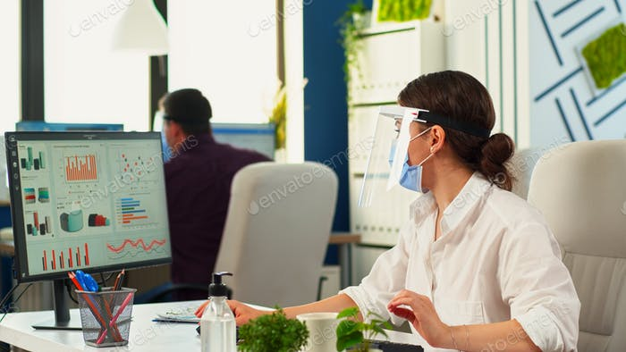 Businesspeople working wearing protection face masks in office room
