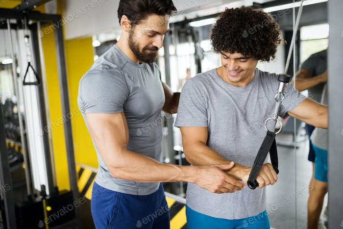 Young handsome man working with help from instructor