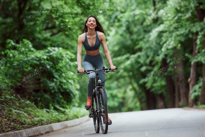Досуг. Женщина-велосипедистка на велосипеде по асфальтированной дороге в лесу в дневное время