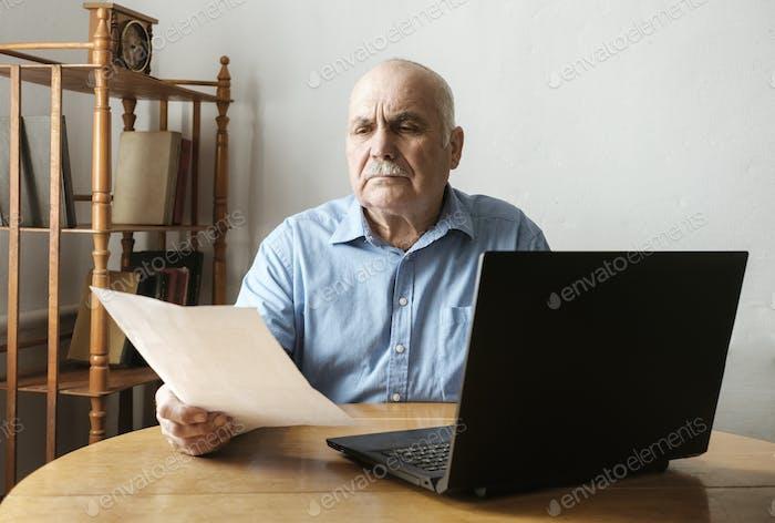 Senior Mann überprüft ein Handheld-Dokument