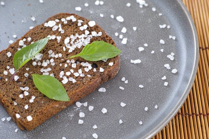 Whole grain organic bread with sea salt and basil leaves