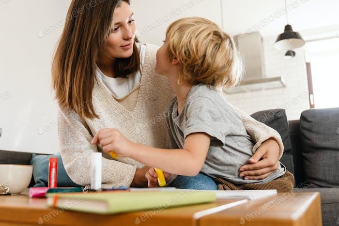 Красивая женщина рисует дома с сыном