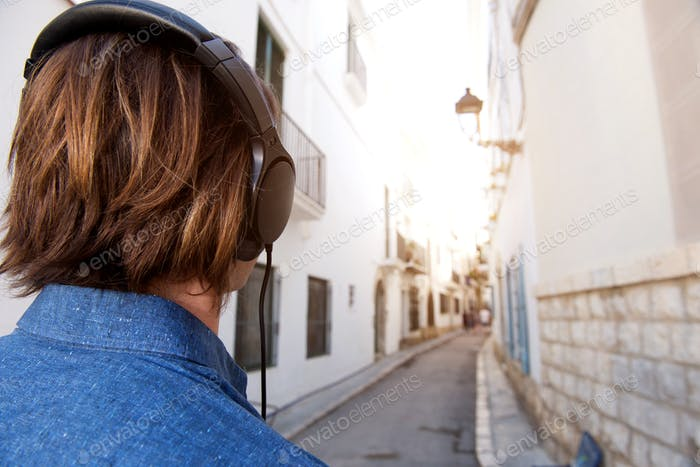 Rear of man with long hair looking at city street with headphones