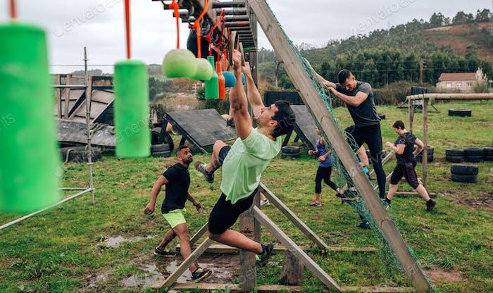 Participant obstacle course doing suspension