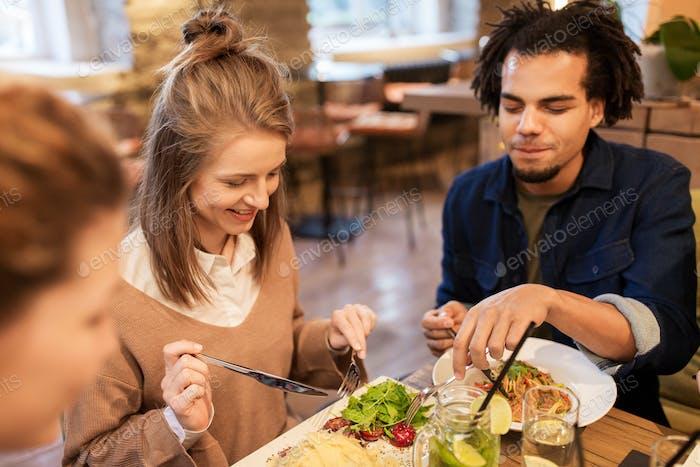 glückliche Freunde essen und trinken im Restaurant
