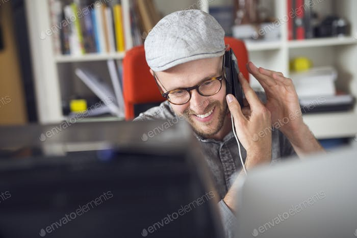 Mid adult man smiling while using phone
