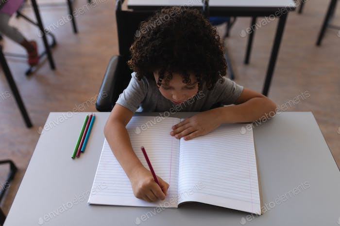 High angle view of schoolboy writing on notebook at desk in classroom of elementary school