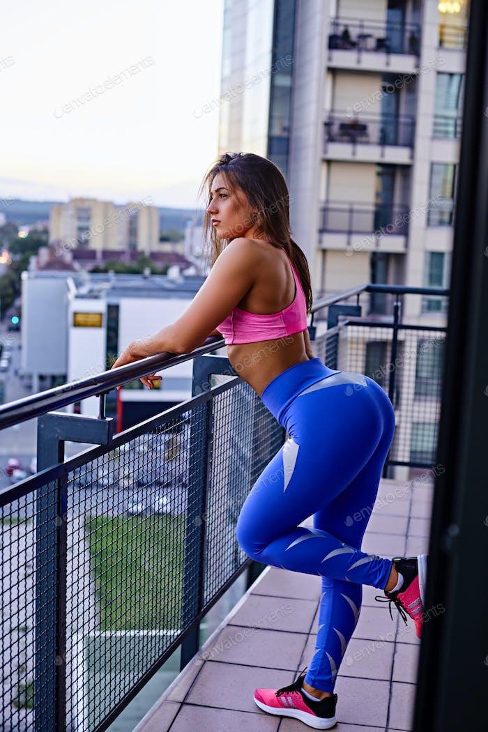 A flexible brunette female on a balcony.