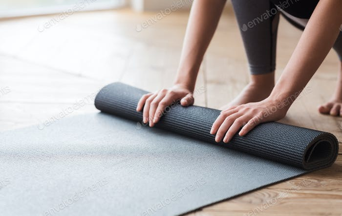 Hands of woman unrolling yoga mat before practice