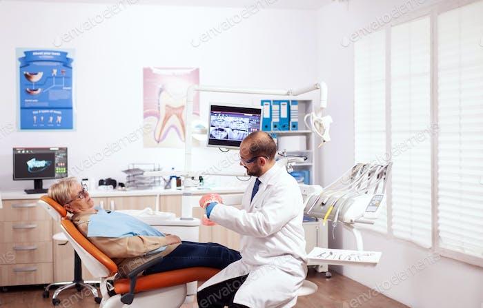 Dentist explaining oral hygiene holding model of cavity