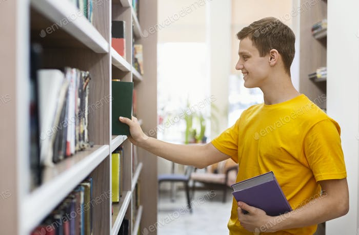 Handsome young man choosing books at bookstore