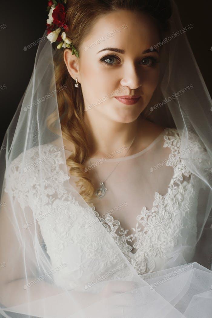 Porträt einer schönen Braut, blonde Braut in elegantem weißem Hochzeitskleid mit Schleier posiert