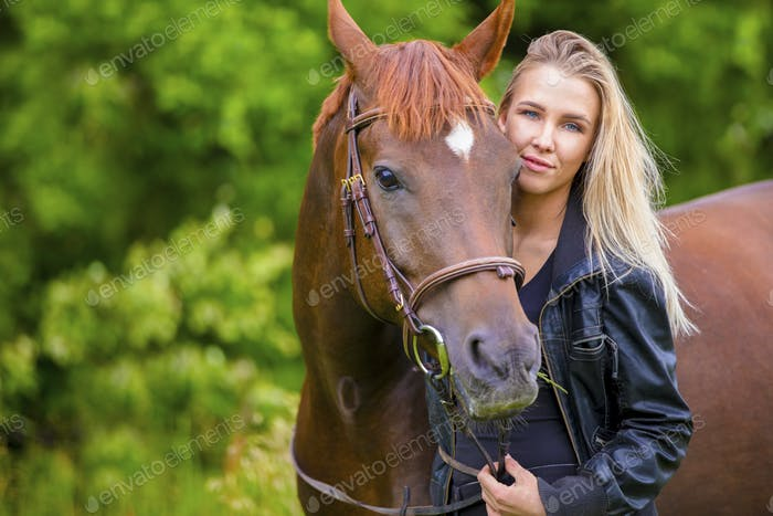 Beautiful smiling woman with her arabian horse in the field