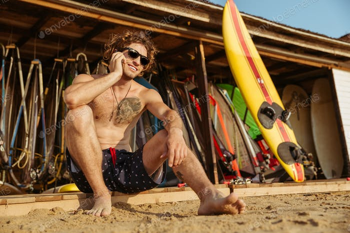 Surfer man in eyeglasses sitting and talking on smartphone outdoors