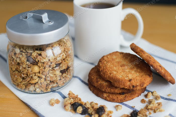 wholemeal oatmeal cookies stack with granola and coffee on napkin