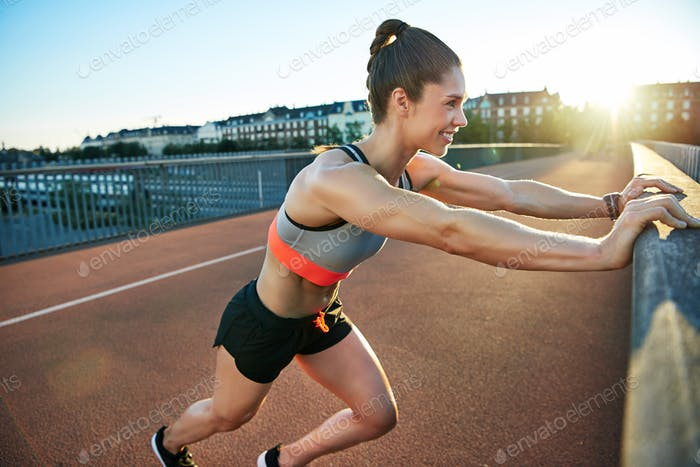 Woman in athletic shorts and top stretches her leg