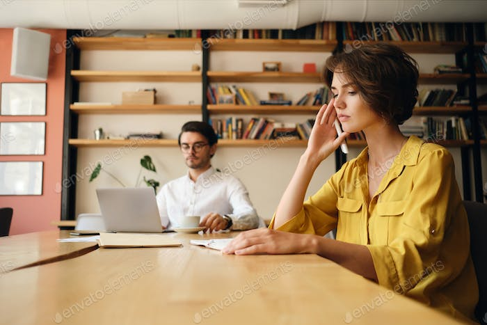 Serious woman sitting at the table with notepad thoughtfully working with colleague in modern office