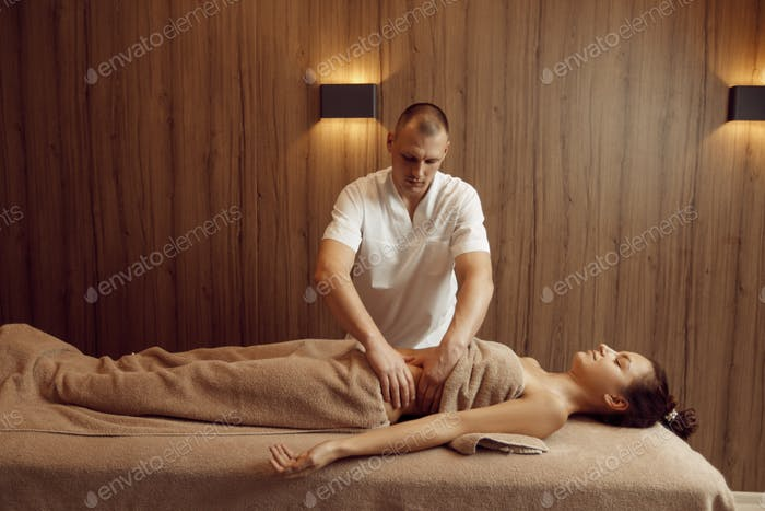 A masseur pampering stomach to young woman