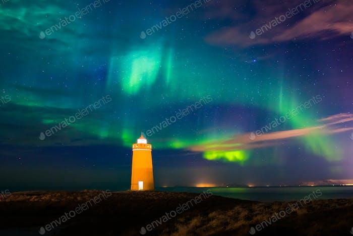 Lighthouse on Reykjanes peninsula under nortern lights. Iceland