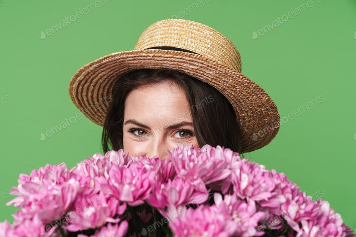 Image closeup of cheerful pretty woman in straw hat holding flowers