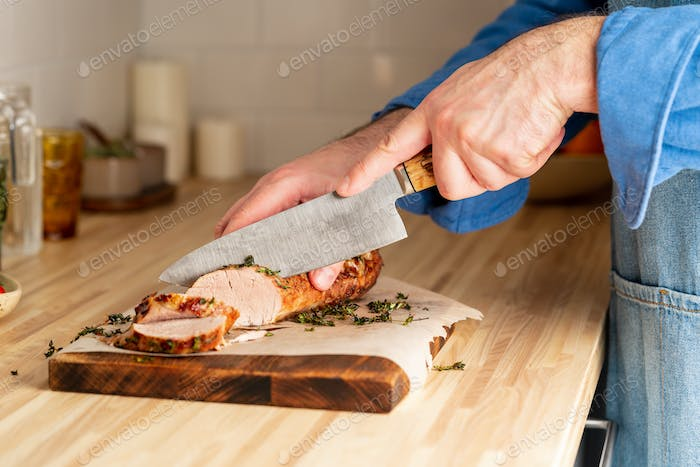 Unrecognizable man cuting with large knife baked pork tenderloin on cutting board
