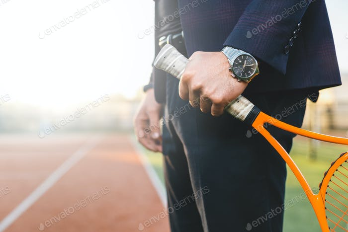 Бизнесмен ручной держит теннисную ракетку
