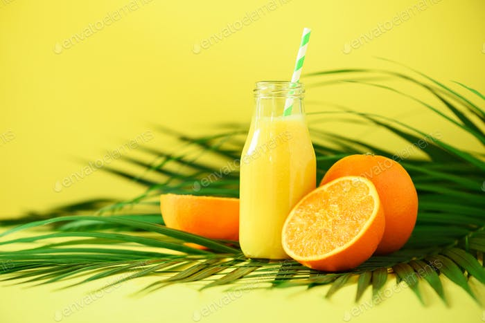 Fresh orange juice in glass jar on yellow background. Copy space. Pop art design, creative summer