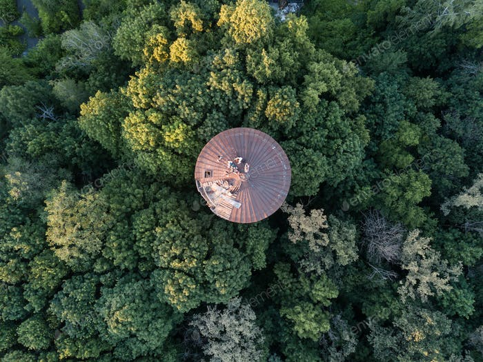 Top view of a round old roof with people around green trees. Aerial view from the drone